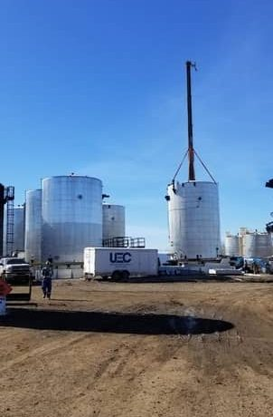 A picture of a Ultimate Energy Controls trailer and tank being lifted on an industrial electrical job in Grande Prairie area.